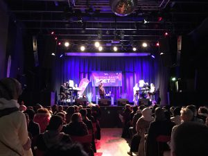 Bild på en scen med jury och presentatör för Ortens Bästa Poet 2016 på Arena 305